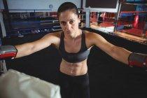 Портрет уверенной женщины-боксера, стоящей на ринге в фитнес-студии — стоковое фото