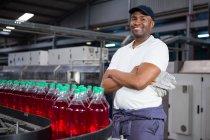 Портрет чоловічого працівника з обіймами перетинають стоячи пляшок на виробничої лінії в завод — стокове фото