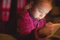 Fille d'âge élémentaire en utilisant une tablette numérique dans la chambre à coucher à la maison, gros plan — Photo de stock