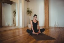 Femme pratiquant le yoga dans un studio de fitness — Photo de stock