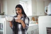 Женщина с мобильного телефона во время завтрака на кухне дома — стоковое фото
