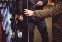 Close-up de casal selecionando esqui juntos em uma loja — Fotografia de Stock