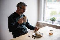 Uomo che utilizza il telefono cellulare mentre prende una tazza di caffè a casa — Foto stock