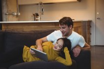 Cheerful couple lying together on sofa using digital tablet in living room — Stock Photo