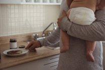 Partie médiane du père préparant le petit déjeuner tout en tenant bébé fils dans la cuisine — Photo de stock