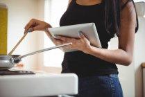 Sezione centrale della cucina femminile e utilizzando tablet digitale in cucina — Foto stock