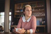 Mulher segurando xícara de café no café — Fotografia de Stock