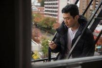 Uomo che utilizza il telefono cellulare in balcone — Foto stock