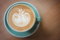 Cup of coffee with beautiful latte art on wooden table — Stock Photo