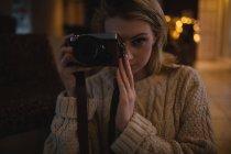 Женщина фотографирует дома на цифровую камеру — стоковое фото