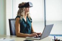 Бизнес-менеджер использует гарнитуру виртуальной реальности и работает на ноутбуке в офисе — стоковое фото