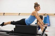 Mulher adulta média exercitando com treinador em reformador no ginásio — Fotografia de Stock
