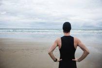 Спортсмен в купальнике, стоящий с рукой на бедре на пляже — стоковое фото