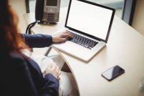 Обрезанный вид беременной бизнесвумен с помощью ноутбука в офисе — стоковое фото