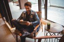 Людина сидить на стільці і використовувати цифровий планшетний у кафе — стокове фото