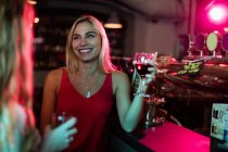 Women interacting while having a glasses of wine at counter in bar — Stock Photo