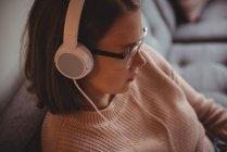 Femme assise sur un canapé écoutant de la musique sur un casque dans le salon à la maison — Photo de stock