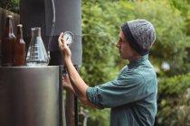 Людина перевірка оцінити при виготовленні пива в будинку пивоварні — стокове фото