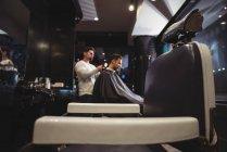 Парикмахерская высушивает волосы клиентов в парикмахерской — стоковое фото