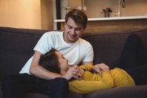 Couple joyeux couché ensemble sur le canapé dans le salon à la maison — Photo de stock