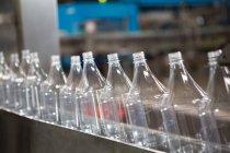 Ряд пустых бутылок на производственной линии в обрабатывающей промышленности — стоковое фото