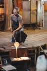 Glassblower working over a molten glass at glassblowing factory — Stock Photo