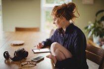 Женщина с помощью цифрового планшета дома — стоковое фото