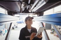 Female mechanic using digital tablet under a car in repair garage — Stock Photo