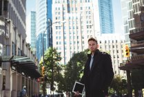 Uomo d'affari con un tablet digitale in piedi sulla strada durante il giorno — Foto stock