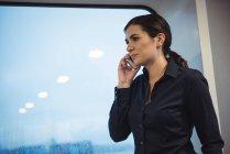 Красивая деловая женщина разговаривает по телефону, стоя в поезде — стоковое фото