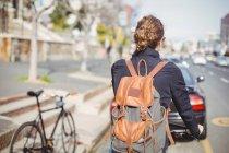 Vista traseira de uma mulher andando de bicicleta na estrada — Fotografia de Stock