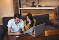Пара, сидящая на диване и обсуждающая финансовые документы в гостиной дома — стоковое фото
