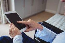 Primer plano del hombre mayor sentado en silla de ruedas y usando tableta digital en casa - foto de stock