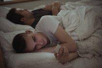 Людина перевірка мобільний телефон лежачи на ліжку з гей партнер в спальні — стокове фото