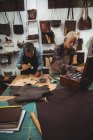 Atentos artesãos martelando couro na oficina — Fotografia de Stock