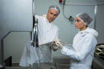 Carniceiros, mantendo o registro na área de transferência na fábrica de carne — Fotografia de Stock