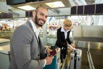 Усміхаючись бізнесмен, стоячи з паспортом при супутніх прилипання тег багажу в терміналі аеропорту — стокове фото