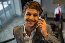 Бизнесмен на эскалаторе разговаривает по мобильному телефону в аэропорту — стоковое фото