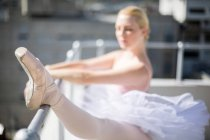 Ballerina dehnt sich auf einem Barre, während sie im Studio Balletttanz übt — Stockfoto