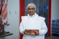 Портрет мясника с подносом для мяса на мясокомбинате — стоковое фото
