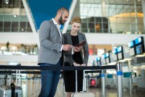 Business people checking their passport at check-in counter in airport terminal — Stock Photo