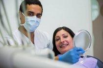 Dentiste tenant miroir devant le patient à la clinique — Photo de stock