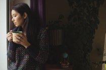 Mulher bonita tendo café perto da janela em casa — Fotografia de Stock