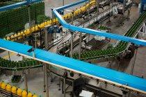 Высокий угол обзора бутылок холодных напитков на производственной линии на заводе — стоковое фото
