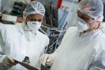 Macellai che interagiscono tra loro in fabbrica di carne — Foto stock