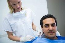 Стоматолог, помогающий пациенту носить зубной фартук в клинике — стоковое фото
