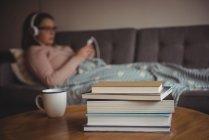 Pile de livres sur la table tandis que la femme écoute de la musique en arrière-plan à la maison — Photo de stock