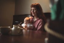 Mother with baby using mobile phone in cafe — Stock Photo