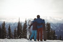 Rear view of couple holding snowboard at mountain during winter against sky — Stock Photo