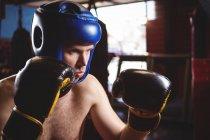 Boxer au casque en position de boxe dans un studio de fitness — Photo de stock